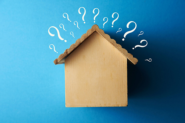 Image of house with questions marks around it. Does Homeowners Insurance Cover Roof Leaks?